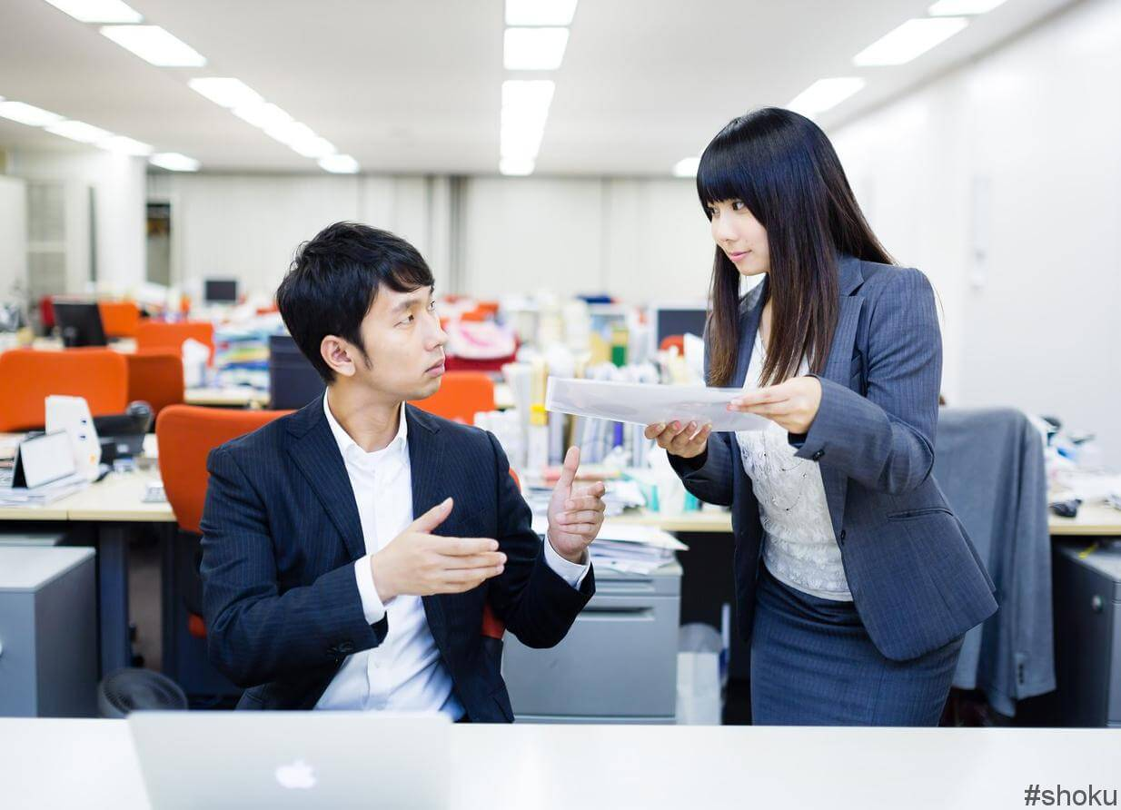 営業事務の仕事中に上司に資料を渡す女性