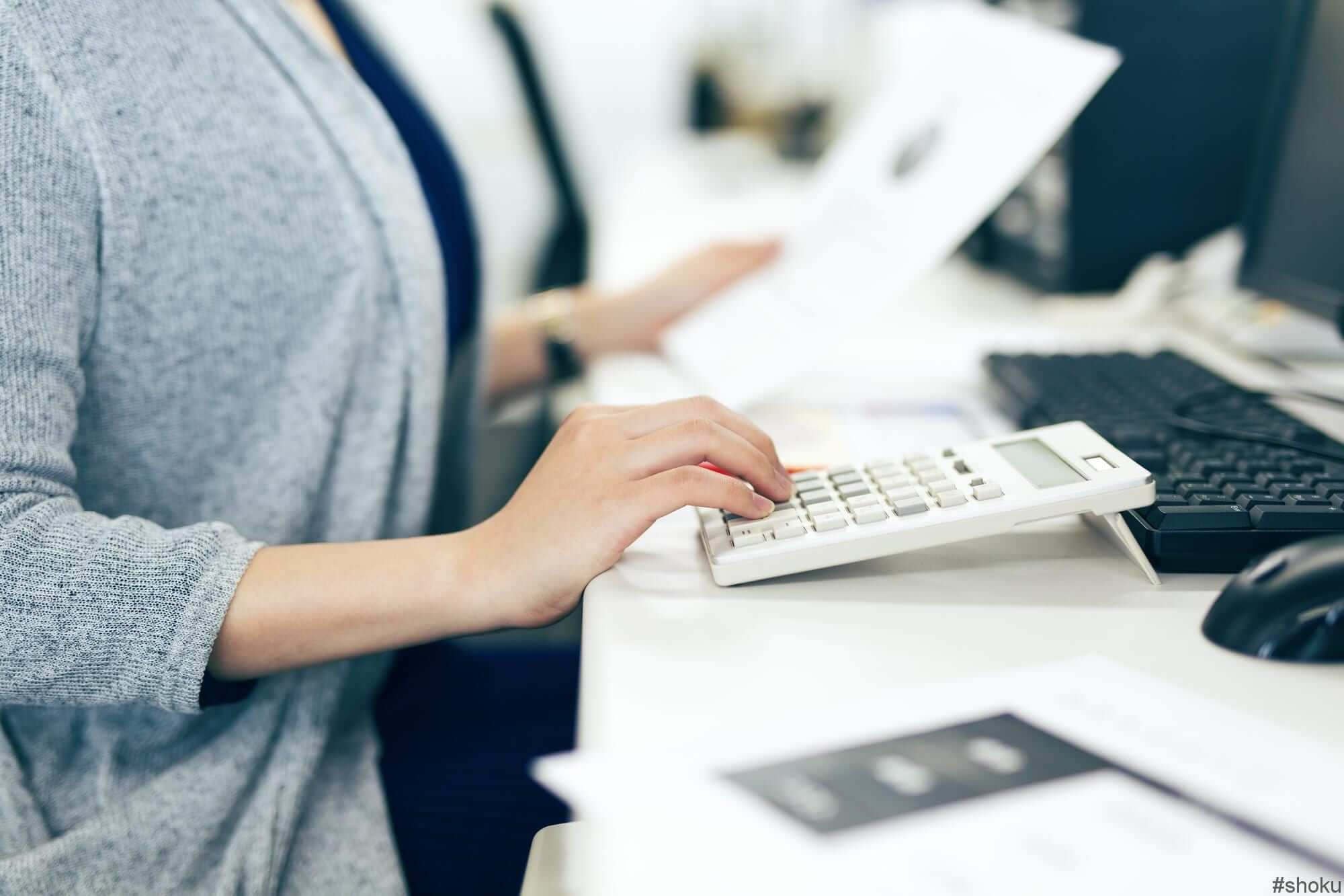 時給が高い経理職の求人を見て計算する女性